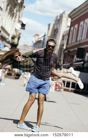 Young man hipster with handsome bearded face in sunglasses holding pretty cute girl both wearing fashion casual clothes on city street background outdoor