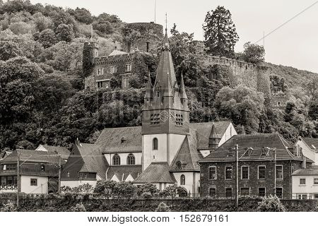 Niederheimbach village in the Unesco World Heritage area of the Rhine Valley in cloudy weather. Black and white photography sepia toned.