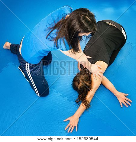 Female athlete stretching with physical therapist, toned image