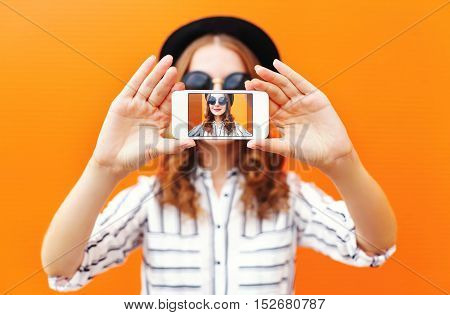 Fashion Cool Girl Taking Picture Self Portrait On Smartphone Over Colorful Orange Background