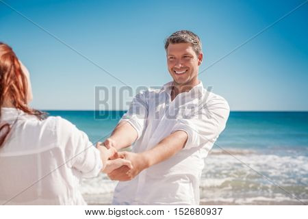 boyfriend dancing with girlfriend on the beach