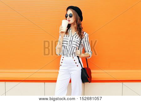 Fashion Pretty Woman With Coffee Cup Wearing A Black Hat White Pants Handbag Clutch Over Colorful Or