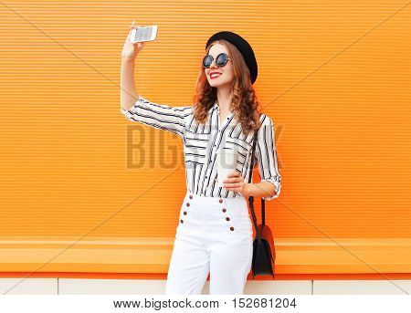 Trendy Young Woman Model Taking Picture Self Portrait On Smartphone Wearing A Black Hat White Pants