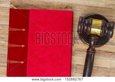Wooden Law Gavel and legal book on wooden desktop, top view