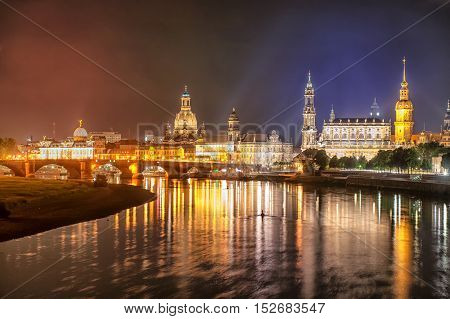 Old town of Dresden with the Castle Zwinger and Frauenkirche reflecting in Elbe river at night time Germany