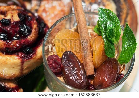granola in the glass with dried apricots dates cinnamon and mint with a blurred background