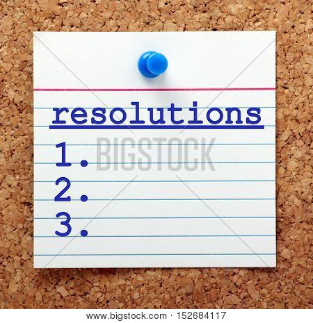 List of Resolutions on a note card pinned to a cork notice board as a reminder of your plans to make changes in the New Year