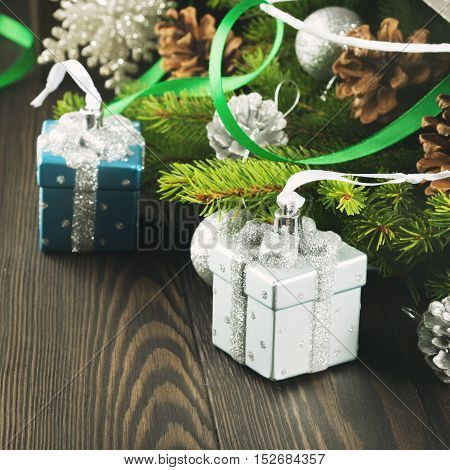 Fir tree branches with christmas gift shaped baubles, pine cones and green ribbons on dark wooden background. Square image