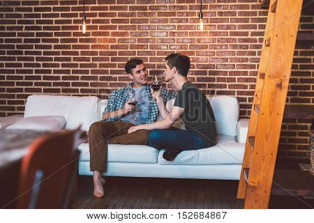 Affectionate young gay couple sitting at home together on their living room sofa talking and drinking red wine