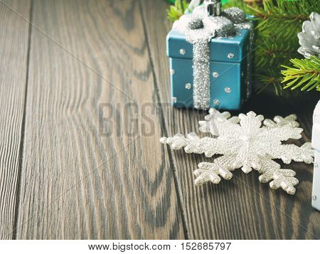 Fir tree branches with christmas gift shaped baubles, pine cones and snow flake ornament on dark wooden background. Copy space. Toned image