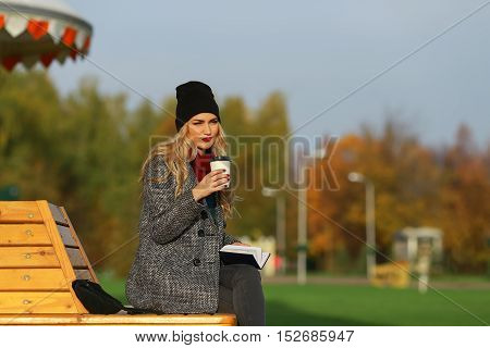 Trendy woman in stylish coat sitting on the bench in city park. Urban scene outdoors. Drinking takeaway coffee and writing or drawing something in notebook.
