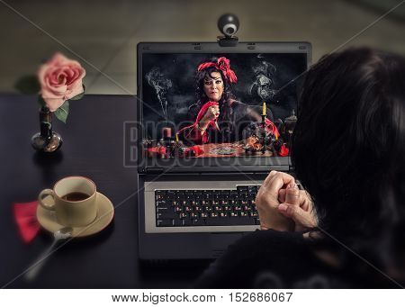 Woman sitting at black coffee desk with laptop. She looks at gypsy female sorcerer who doing deadly curse ritual with a knife and playing cards on the screen
