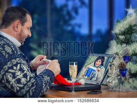 Two friends having holiday party on Christmas Eve online. Middle-aged man in Scandinavian sweater sits opposite laptop and looking at black-haired woman there. They are going to wear Santa blue hats