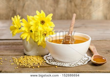 Yellow Flowers And Bee Products (honey, Pollen) On Wooden Background