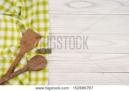 Spoon and spatula in the kitchen napkin and white table. Top view.