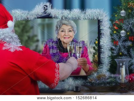 Santa Claus wishes smiling lonely senior woman a Merry Christmas and offers a toast with white sparkling wine during online video chat