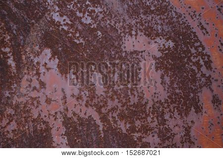 Spotted rusty shabby metallic sheet with peeling red paint. Metal texture