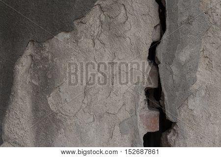 Gray obsolete plastered wall divided by wide split. Rough uneven texture
