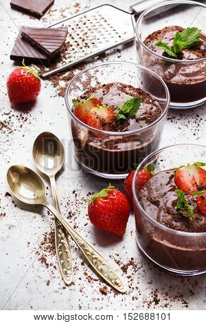 Food and drink, dessert sweet concept. Chocolate mousse with mint and strawberries in glass on rustic table. Selective focus