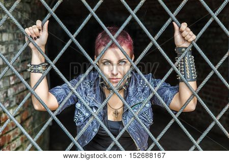 young pretty punk girl standing behind bars