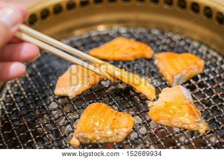 Salmon fish steak cooking over charcoal grill. Close up at chopstick Salmon fish steak.