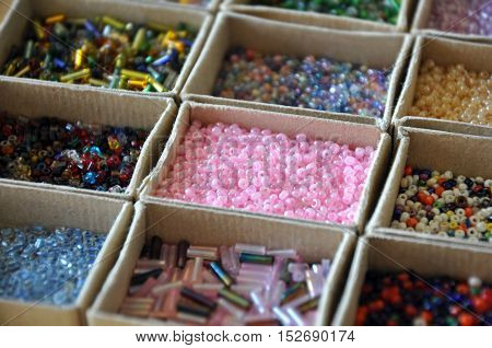 Many kinds of beads of different colors and shapes in cardboard boxes in perspective. Selective focus.