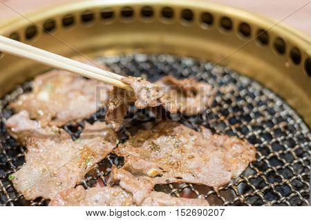 Pork slice steak cooking over charcoal grill. Close up at chopstick Pork slice steak.