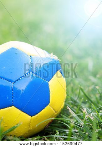 old football on the field and small gravel with sunshine
