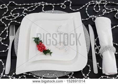 Christmas dinner table setting with white porcelain plates, holly, silver bead decorations, cutlery and linen napkin with ring over dark wood background.