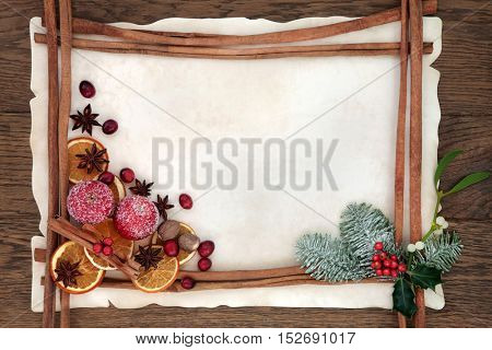 Christmas abstract background border with cinnamon sticks, spices, dried orange, apple and cranberry fruit with holly, fir and mistletoe on parchment paper over oak wood.