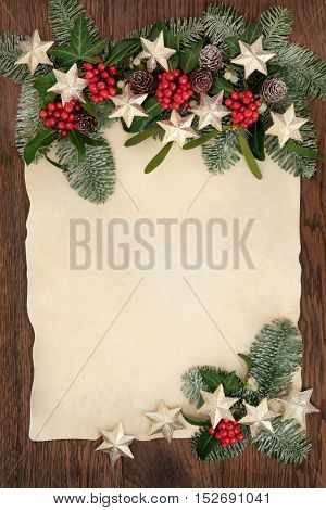 Christmas abstract background border with gold star decorations, holly, ivy, mistletoe and snow covered blue spruce fir on old parchment paper over oak wood.