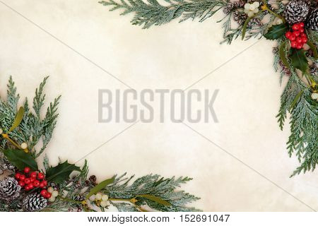 Winter and christmas background border with holly, ivy, mistletoe, snow covered  cedar cypress and pine cones on old parchment paper.