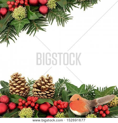 Christmas decorative border with red bauble and robin decorations, holly, ivy, gold pine cones and winter greenery over white background.