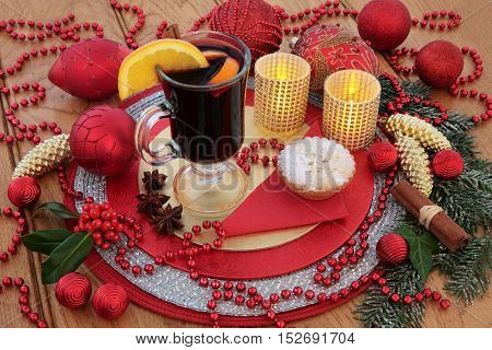 Christmas  mulled wine, mince pie, red and gold bauble decorations, candles, fruit and spices, holly and snow covered winter greenery on oak background.