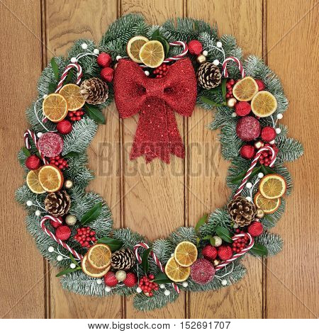 Christmas wreath with red bow decoration, dried fruit, candy canes, baubles, holly, mistletoe, pine cones and snow covered blue spruce fir over oak wood front door background.