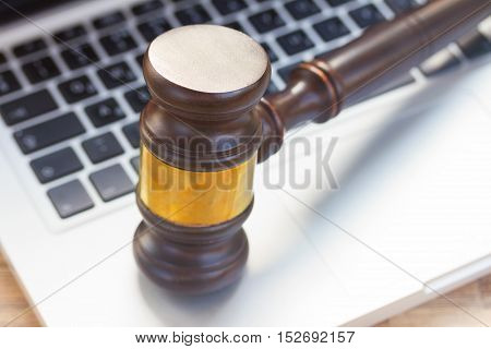 Wooden law gawel on laptop keyboard, judgement concept
