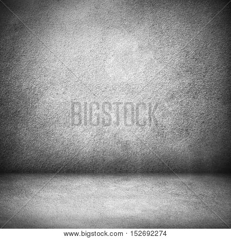 Abstract stonework background texture with old weathered dark stucco black paint stone cement wall in rural room. Grungy cold rock surface in hard grime empty place with gray granite dull light floor.