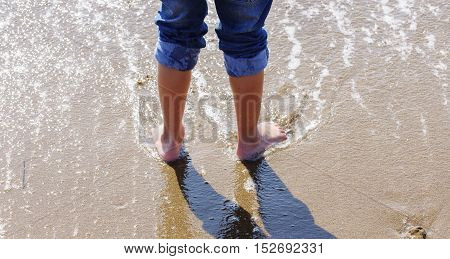 feet in water. child on the beach