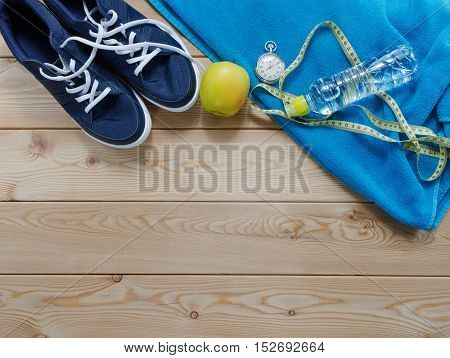 Fitness concept with sneakers notebook stopwatch apples towel and measure tape
