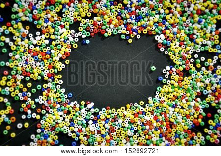 Multicolor beads on a dark surface with space for text in the middle. Selective focus.