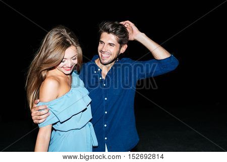 Happy beautiful young couple standing and embracing at night on the beach