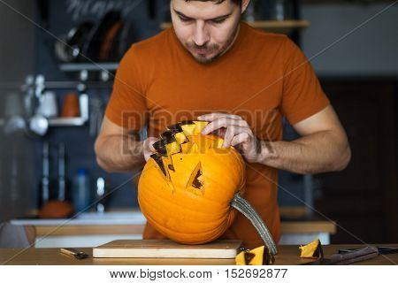 Man preparing to celebrate Halloween Day. He pulls up in his kitchen lantern jack of ripe pumpkins.