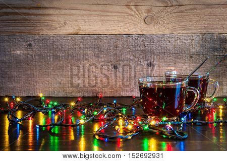 Christmas background with cups of tea and lights on wood texture with place for text