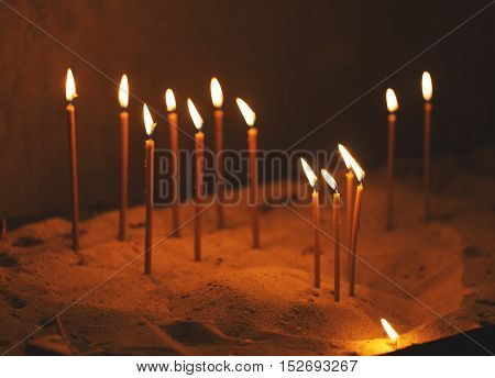 Church candles in sand horizontal religious background.