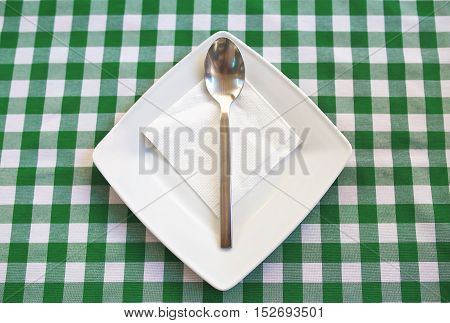 Empty Square Plate With Silver Spoon.