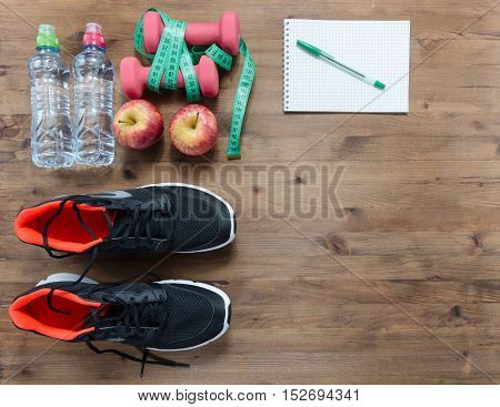 Fitness concept with sneakers notebook stopwatch apples towel dumbbells and measure tape