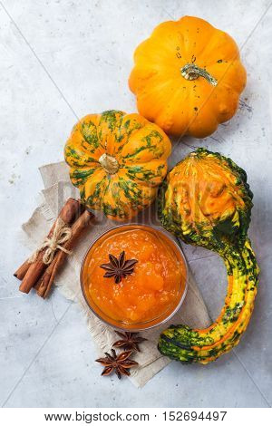 Seasonal, food and drink concept. Autumn fall homemade pumpkin jam with spices in glass on rustic table. Selective focus, top view flat lay overhead