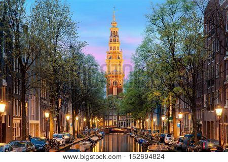 Amsterdam Zuiderkerk church tower at the end of a canal in the city of Amsterdam Netherlands at night . Amsterdam is the capital and most populous city of Netherlands