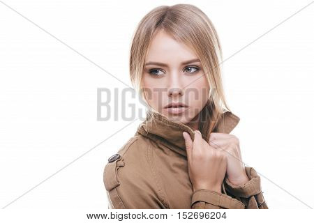 Autumn fashion. Attractive young woman in coat adjusting her collar and looking away while standing against white background