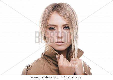 Autumn fashion. Attractive young woman in coat adjusting her collar and looking at camera while standing against white background